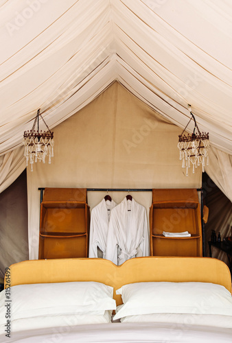 Luxury Safari tent camp bedroom interior in Serengeti Savanna forest - Glamping travel in Africa wild forest Wall mural