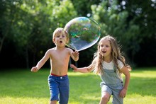 Brother And Sister Chasing Bubbles