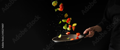 Fototapeta Banner. Seafood, roasting red fish by the chef, salmon or trout, tuna, pink salmon with vegetables, Brussels sprouts. Freezing in motion. Recipe book, cooking, gastronomy, restaurant service obraz