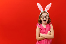Happy Easter. Funny Cheerful Little Girl In Rabbit Ears And Glasses On A Red Background. The Child Crossed His Arms And Looks At The Camera