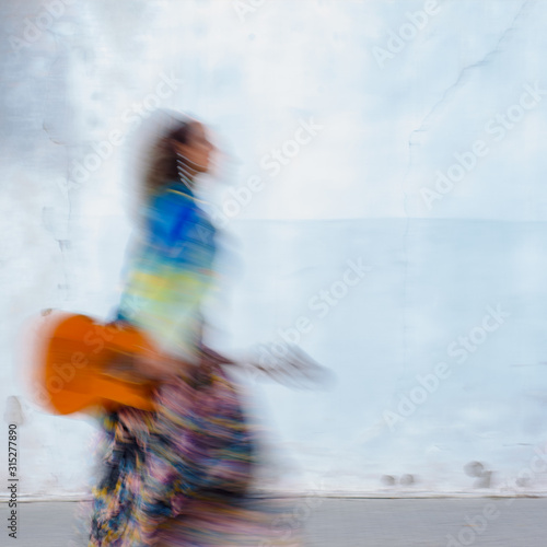 Photographie Artistic woman with guitar on city street