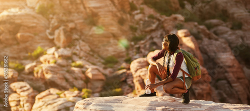 Canvas Print athletic african american woman backpacker on top of tall cliff at red rock cany