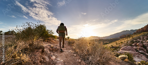 Photographie athletic african american woman hiking through red rock canyon in nevada at suns