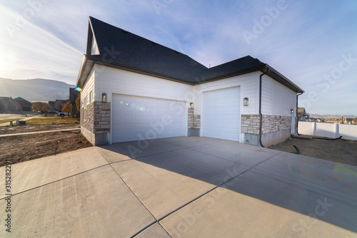 Fotografie, Obraz Two garages with paved forecourt and white doors