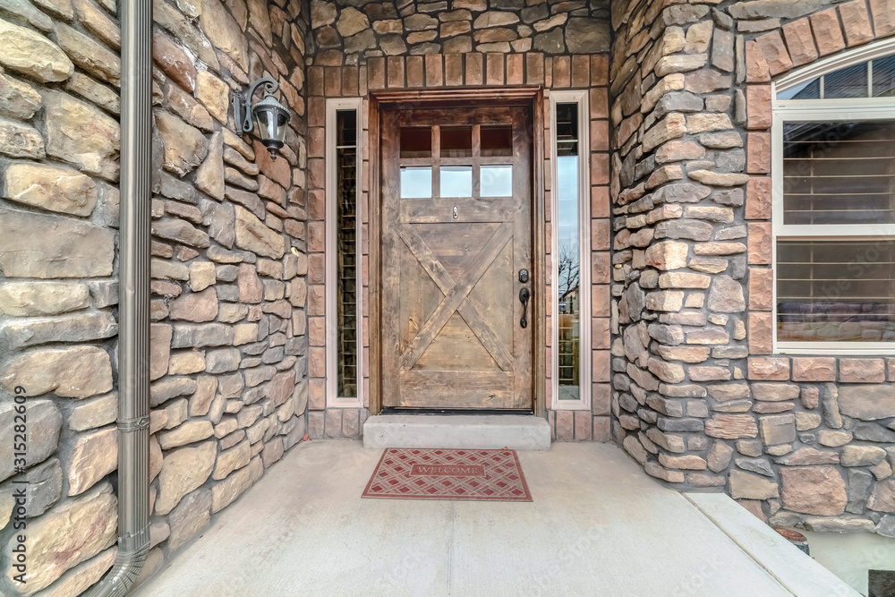 Fototapeta Entrance door to home with stone brick walls