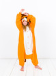 pretty blonde girl with cozy lion costume is posing in the studio in front of white wall