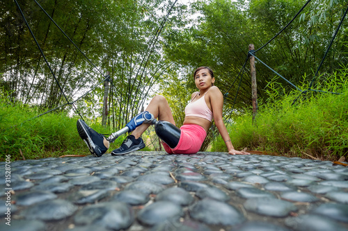Leg amputated Asian girl posing with confident after her workout routine in natu Wallpaper Mural