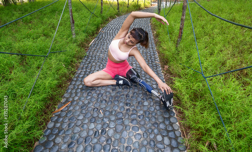 Leg amputated Asian girl working out in nature park to gain body strength Wallpaper Mural