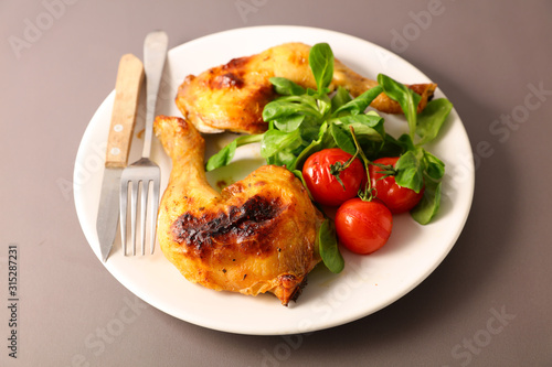 Fototapeta grilled chicken leg and salad in plate obraz