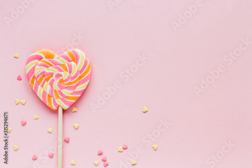 Big striped heart-shaped lollipop and confectionery confetti on a pink background copy space Poster Mural XXL