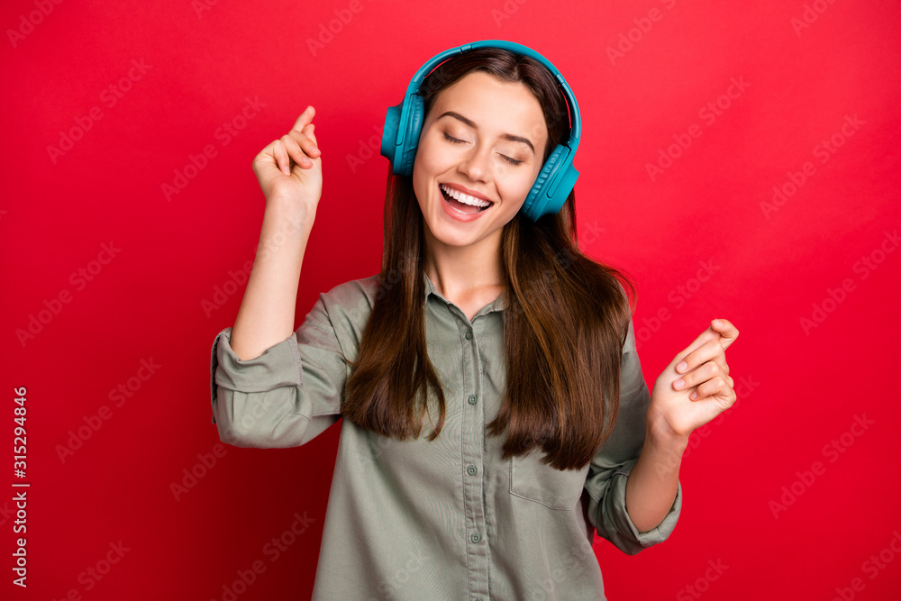 Fototapeta Photo of pretty lady cheerful mood modern technology headphones on ears listen new popular youth song wear casual grey green shirt isolated red color background