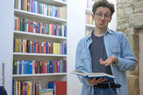 Young studying man with book in his hands standing next to bookshelf and is looking surprised and interrogative in the camera Canvas-taulu