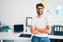 Portrait Of Confident Graphic Designer Leaning On Desk In Office With Arms Crossed