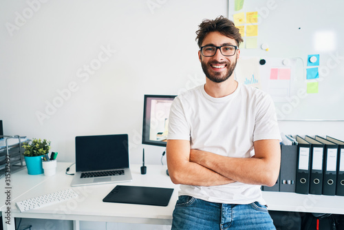 Obraz Portrait of confident graphic designer leaning on desk in office with arms crossed - fototapety do salonu
