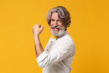 Side View Of Elderly Gray-haired Mustache Bearded Man In White Shirt Bow Tie Posing Isolated On Yellow Orange Background In Studio. People Lifestyle Concept. Mock Up Copy Space. Doing Winner Gesture.