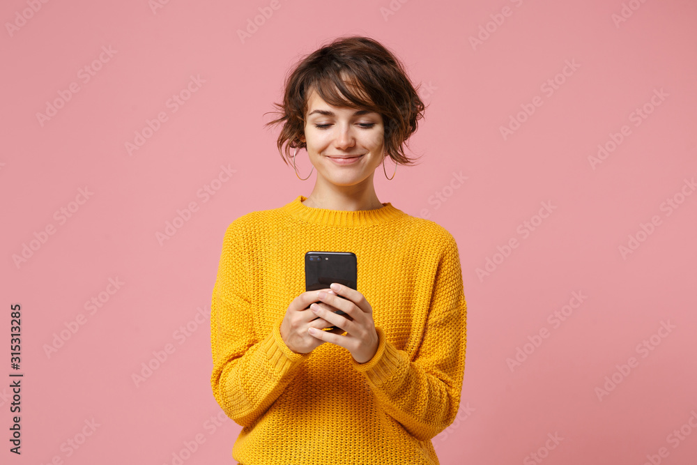 Fototapeta Smiling young brunette woman girl in yellow sweater posing isolated on pastel pink wall background studio portait. People lifestyle concept. Mock up copy space. Using mobile phone, typing sms message.