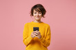 canvas print picture - Smiling young brunette woman girl in yellow sweater posing isolated on pastel pink wall background studio portait. People lifestyle concept. Mock up copy space. Using mobile phone, typing sms message.