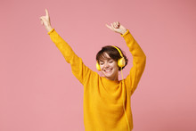 Smiling Young Brunette Woman Girl In Yellow Sweater Posing Isolated On Pastel Pink Wall Background Studio Portait. People Lifestyle Concept. Mock Up Copy Space. Listen Music With Headphones, Dancing.