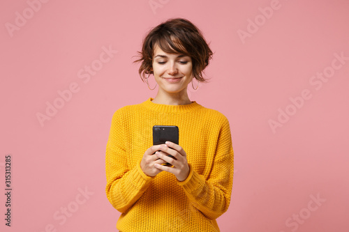 Leinwand Poster Smiling young brunette woman girl in yellow sweater posing isolated on pastel pink wall background studio portait