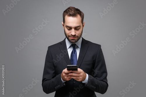 Handsome young business man in classic black suit shirt tie posing isolated on grey background. Achievement career wealth business concept. Mock up copy space. Using mobile phone typing sms message.