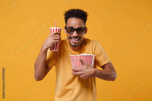 Платно Scared young african american guy in 3d imax glasses posing isolated on yellow orange background
