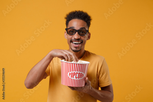 фотография Cheerful young african american guy in 3d imax glasses posing isolated on yellow orange background in studio