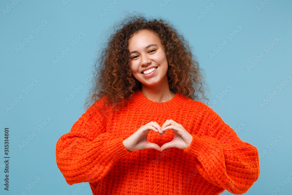 Fototapeta Smiling young african american girl in casual orange knitted clothes isolated on pastel blue background. People lifestyle concept. Mock up copy space. Showing shape heart with hands, heart-shape sign.