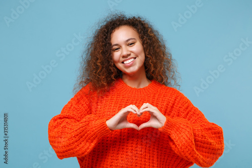 Fototapeta Smiling young african american girl in casual orange knitted clothes isolated on pastel blue background. People lifestyle concept. Mock up copy space. Showing shape heart with hands, heart-shape sign. obraz