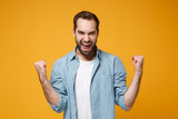 Joyful young bearded man in casual blue shirt posing isolated on yellow orange wall background, studio portrait. People sincere emotions lifestyle concept. Mock up copy space. Doing winner gesture.