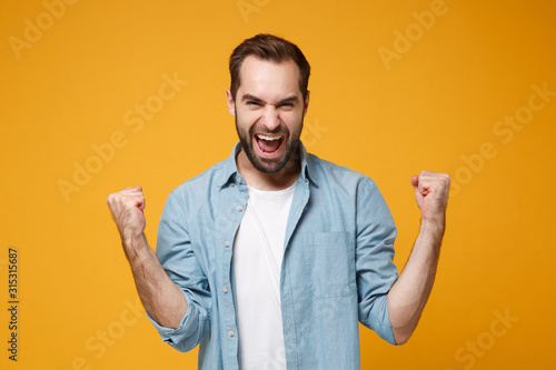 Joyful young bearded man in casual blue shirt posing isolated on yellow orange wall background, studio portrait Fototapeta