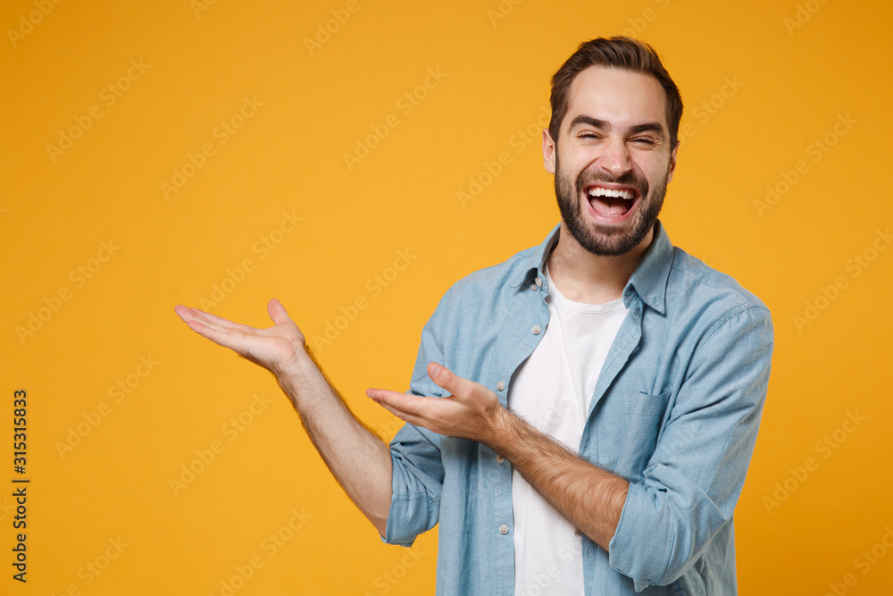 Fototapeta Laughing young bearded man in casual blue shirt posing isolated on yellow orange wall background, studio portrait. People sincere emotions lifestyle concept. Mock up copy space. Pointing hands aside.