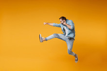Side View Of Crazy Young Bearded Man In Casual Blue Shirt Posing Isolated On Yellow Orange Background Studio Portrait. People Sincere Emotions Lifestyle Concept. Mock Up Copy Space. Jumping, Fighting.