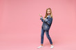 Excited little blonde kid girl 12-13 years old in denim jacket isolated on pastel pink background children studio portrait. Childhood lifestyle concept. Mock up copy space. Point index fingers aside.