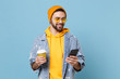 Leinwanddruck Bild - Smiling young hipster guy in fashion jeans denim clothes posing isolated on pastel blue background. People lifestyle concept. Mock up copy space. Using mobile phone, hold paper cup of coffee or tea.