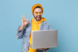 Funny young hipster guy in fashion jeans denim clothes posing isolated on pastel blue wall background. People lifestyle concept. Mock up copy space. Working on laptop pc computer, showing OK gesture.