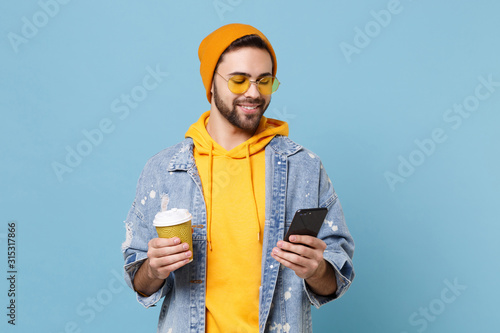 Smiling young hipster guy in fashion jeans denim clothes posing isolated on pastel blue background Obraz na płótnie