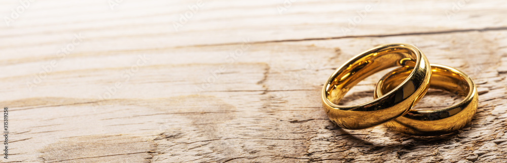 Fototapeta Golden wedding rings on wood