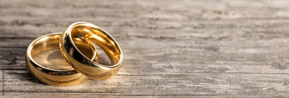 Fototapeta Golden wedding rings on wood