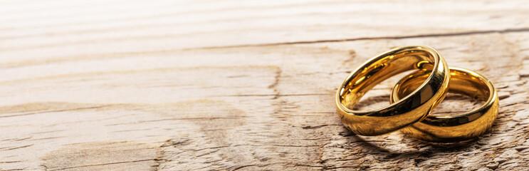 FototapetaGolden wedding rings on wood