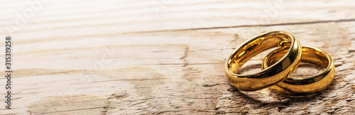 Golden wedding rings on wood - 315319258