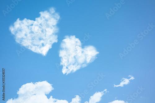 Fototapeta Two clouds in heart shape soar in blue sky
