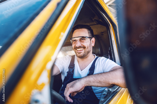 Smiling handsome unshaven worker driving vehicle on construction site Fototapet