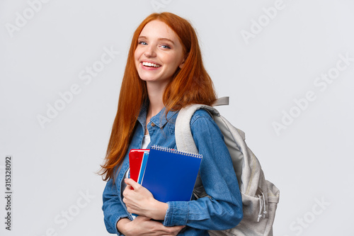 Teenagers, students and education concept. Cheerful lovely redhead female studying, going to univeristy or college, smiling carefree holding backpack and notebooks, standing white background