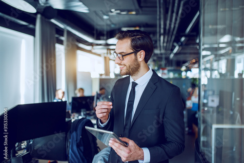 Handsome caucasian bearded smiling businessman in suit and with eyeglasses walking trough company, evaluating employees and holding tablet.
