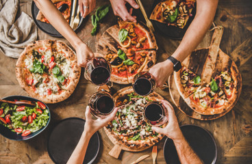 Family or friends having pizza party dinner. Flat-lay of people clinking glas...