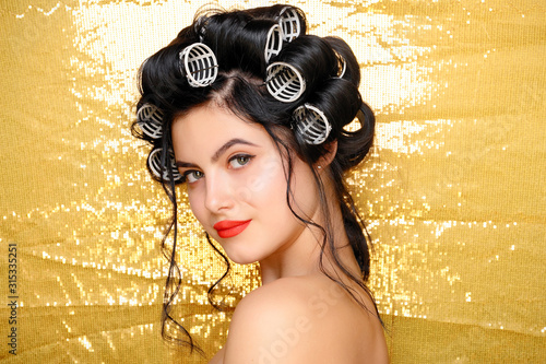 Beautiful Smiling girl in hair curlers isolated on gold Wallpaper Mural