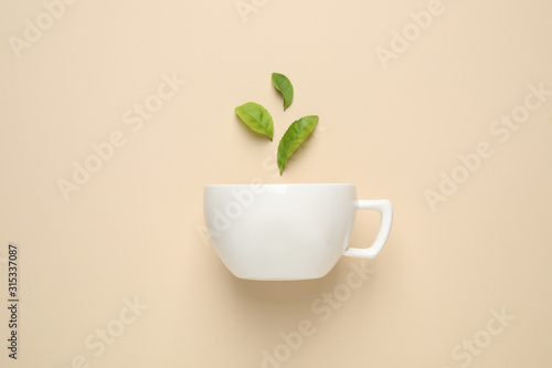 Fresh tea leaves and cup on beige background, top view Canvas Print