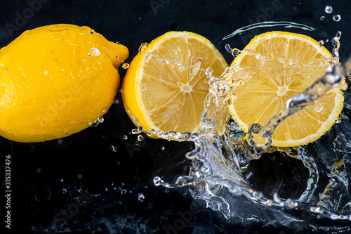 halves of a whole lemon with drops and splashes of water on a black background