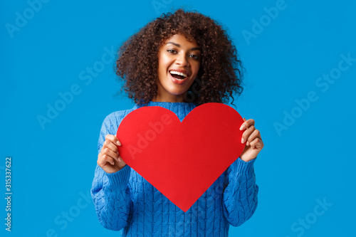 Obraz Lovely and cute african-american pretty woman with afro haircut, holding valentines day card, big heart and smiling, express love and affection, showing true feelings, search soulmate - fototapety do salonu
