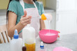 canvas print picture - Little girl mixing ingredients with silicone spatula at table in kitchen, closeup. DIY slime toy